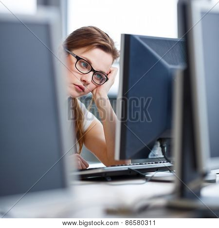 Pretty, female student looking at a desktop computer screen, learning unpleasant news about her exam results. University/office/school concept