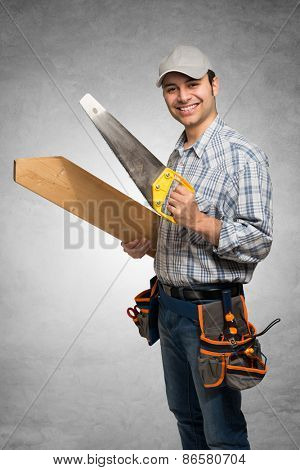 Portrait of a smiling carpenter holding wood planks. Gray grunge background