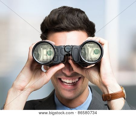 Smiling businessman looking to dollar banknotes through binoculars