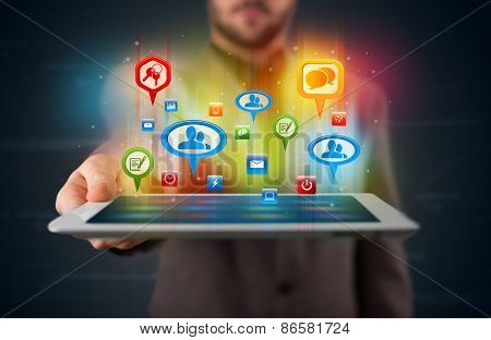 Young businessman presenting modern tablet with colorful social signs and icons