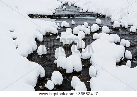 Snow Caps On Boulders In The Mountain River