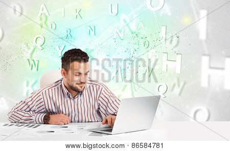 Business man at white desk with green word cloud