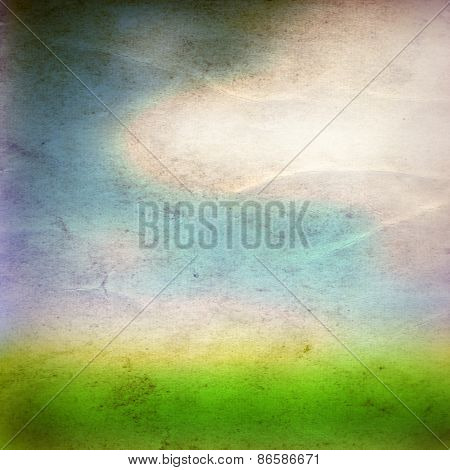 Concept or conceptual green fresh summer or spring grass field over a blue sky background on a vintage old paper