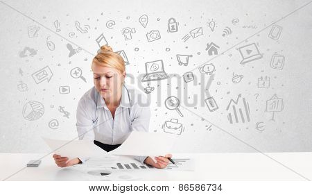 Business woman sitting at table with hand drawn media icons and symbols
