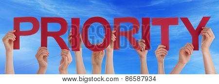 Many People Hands Holding Red Straight Word Priority Blue Sky