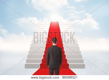 Businessman looking at stairs to heaven