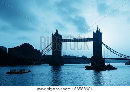 Tower Bridge silhouette over Thames River in London.