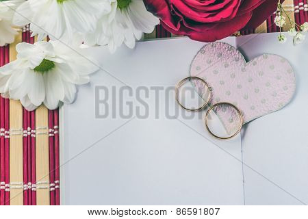wedding rings and paper heart on white paper sheet
