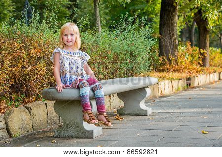 Portrait Of Girl Sitting On Bench In City Park