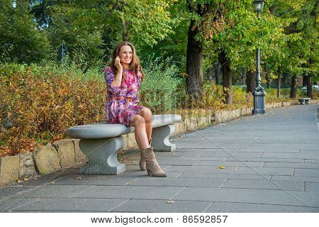 Young Woman Talking Mobile Phone In City Park