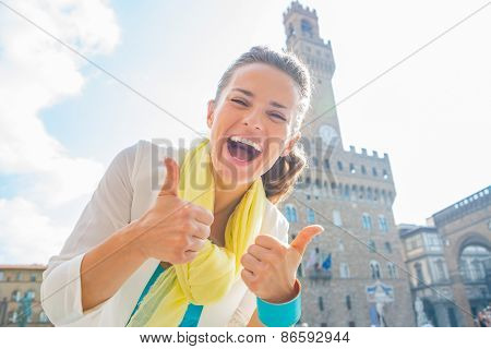 Happy Young Woman Showing Thumbs Up In Front Of Palazzo Vecchio In Florence, Italy