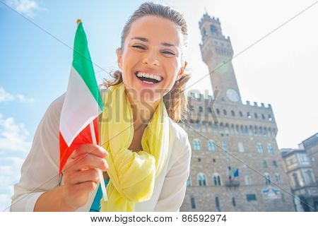 Happy Young Woman With Flag In Front Of Palazzo Vecchio In Florence, Italy