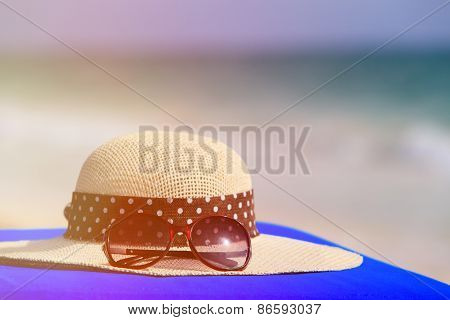 hat and sunglasses on tropical beach