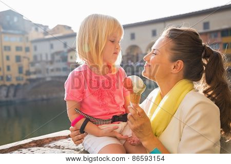 Happy Mother And Baby Girl Eating Ice Cream Near Ponte Vecchio In Florence, Italy