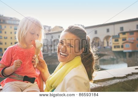 Portrait Of Smiling Mother And Baby Girl Eating Ice Cream Near Ponte Vecchio In Florence, Italy