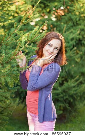 Portrait Of A Girl In A Park Near A Christmas Tree.