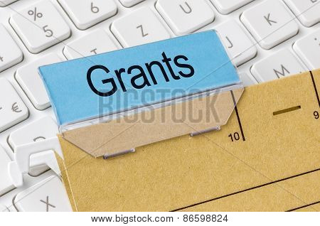 A Brown File Folder Labeled With Grants