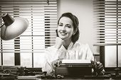 picture of 1950s style  - 1950s style secretary working at office desk and smiling with hand on chin - JPG