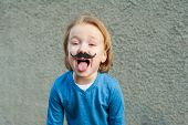 stock photo of cute innocent  - Outdoor close up portrait of a cute little boy with fake moustache - JPG