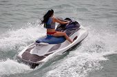foto of jet-ski  - Angled overhead view of a young woman riding on a jet ski rental.