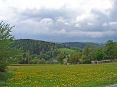 pic of house woods  - hilly landscape in the Erzgebirge in Saxony, Germany, wildflower meadows and woods in the spring, hidden houses