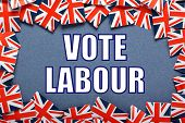 image of labourers  - Miniature Union Jack flags form a border on blue card around the  phrase Vote Labour for the UK General Election - JPG