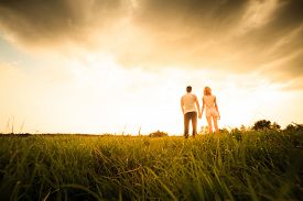 stock photo of girl walking away  - couple walking through the field and holding hands over sunset - JPG
