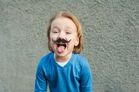 stock photo of tongue  - Outdoor close up portrait of a cute little boy with fake moustache - JPG