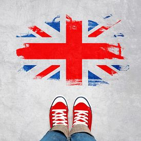 picture of british culture  - British Urban Youth Concept Feet in Red Sneakers from Above Standing in front of Grunge Great Britain Flag - JPG