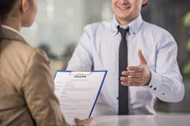 stock photo of candid  - Businesswoman interviewing male candidate for job in office - JPG