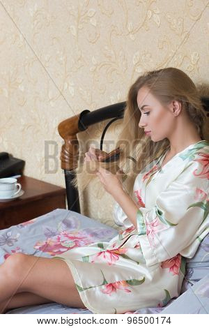 Sexy Young Girl Wearing White Nightdress Combing her Hair While Sitting on a Chair at her Room.