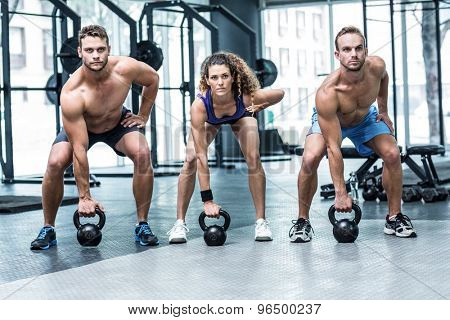Portrait of three muscular athletes about to lift a kettle bell