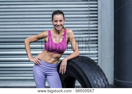 Portrait of a smiling muscular woman leaning on a tire