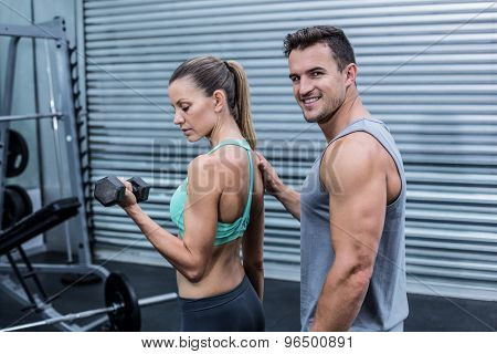 Portrait of a trainer supervising a woman lifting dumbbells