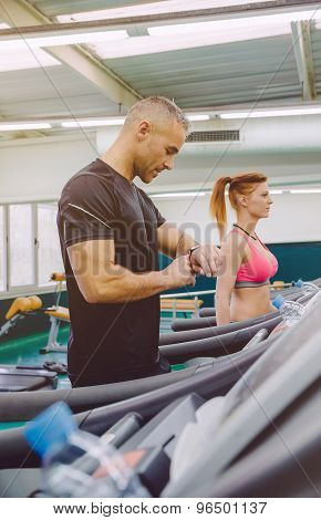Man checking heart rate on watch in treadmill training