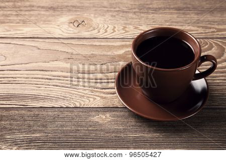 Cup of fresh espresso on wooden table