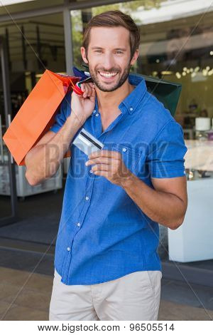 Young happy man holding shopping bags and a credit card after shopping