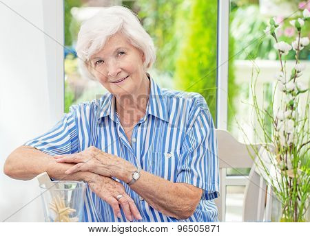 Beautiful senior woman sitting in her winter garden , in the background the garden