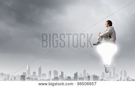 Young businessman sitting on light bulb top and thinking something over