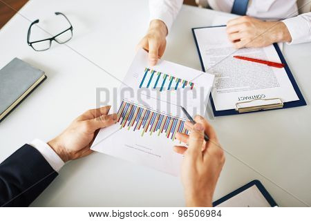 Businessman giving and explaining financial report to boss