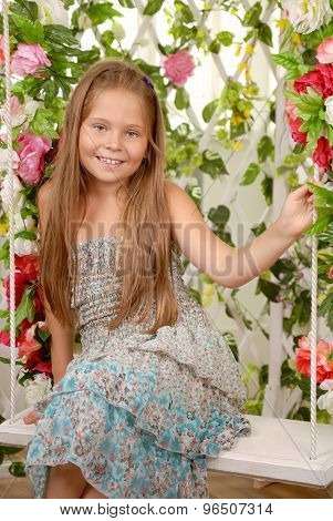 Girl Sits On A Swing In An Flower Arbor