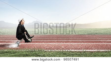Young handsome businessman riding three wheeled bicycle