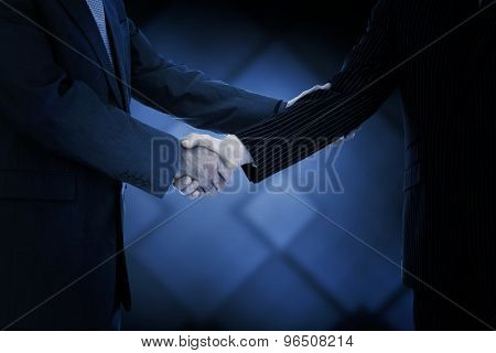Handshake in agreement against dark grey room