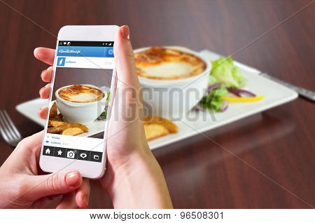 Hand holding smartphone against side view of lasagna with salad and potatoes