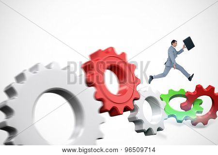Businessman running with a suitcase against white and red cogs and wheels