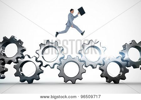 Businessman running with a suitcase against metal cogs and wheels connecting