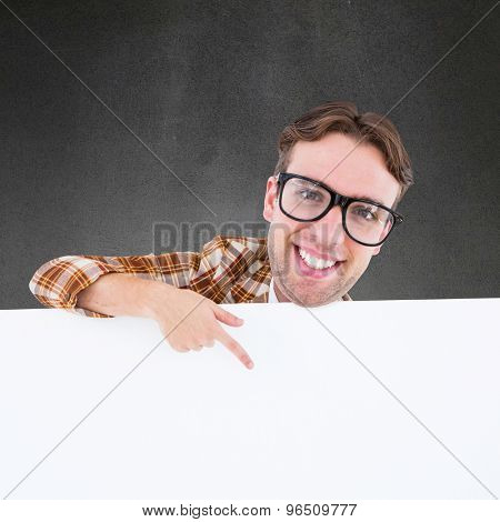 Nerdy businessman pointing to poster against grey room