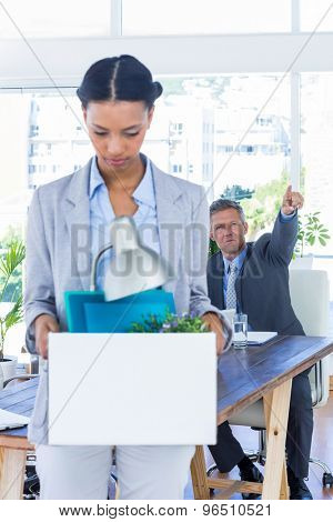A fired businesswoman holding box in office