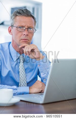Thoughtful businessman looking at camera in office