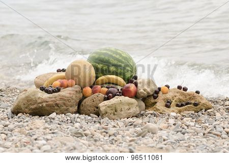 Summer fruits on the rocks against the blue sea.